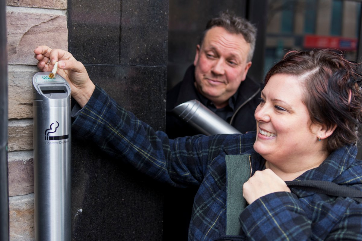 Butt 1 Community Coordinator Donna Reid and Peterborough DBIA Executive Director Terry Guiel dispose of a cigarette butt in one of the new receptacles being given away for downtown businesses.