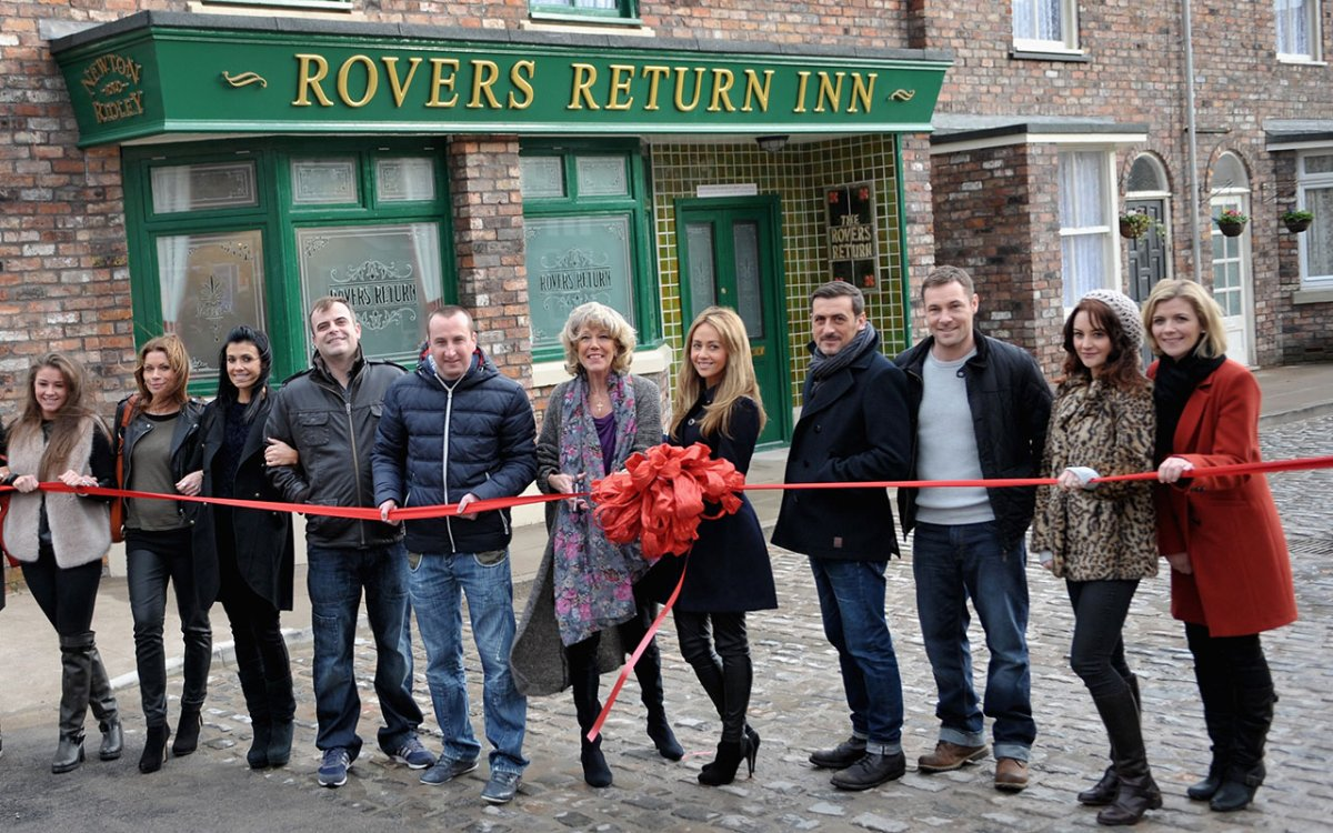 Actress Sue Nicholls cuts a ribbon with 'Coronation Street' cast members to open the Coronation Street set on November 29, 2013 in Manchester, England.