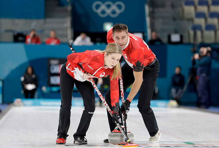 Canada's Kaitlyn Lawes and John Morris sweep the ice during the mixed doubles semi-final curling match against Norway at the 2018 Winter Olympics in Gangneung, South Korea, Feb. 12, 2018.