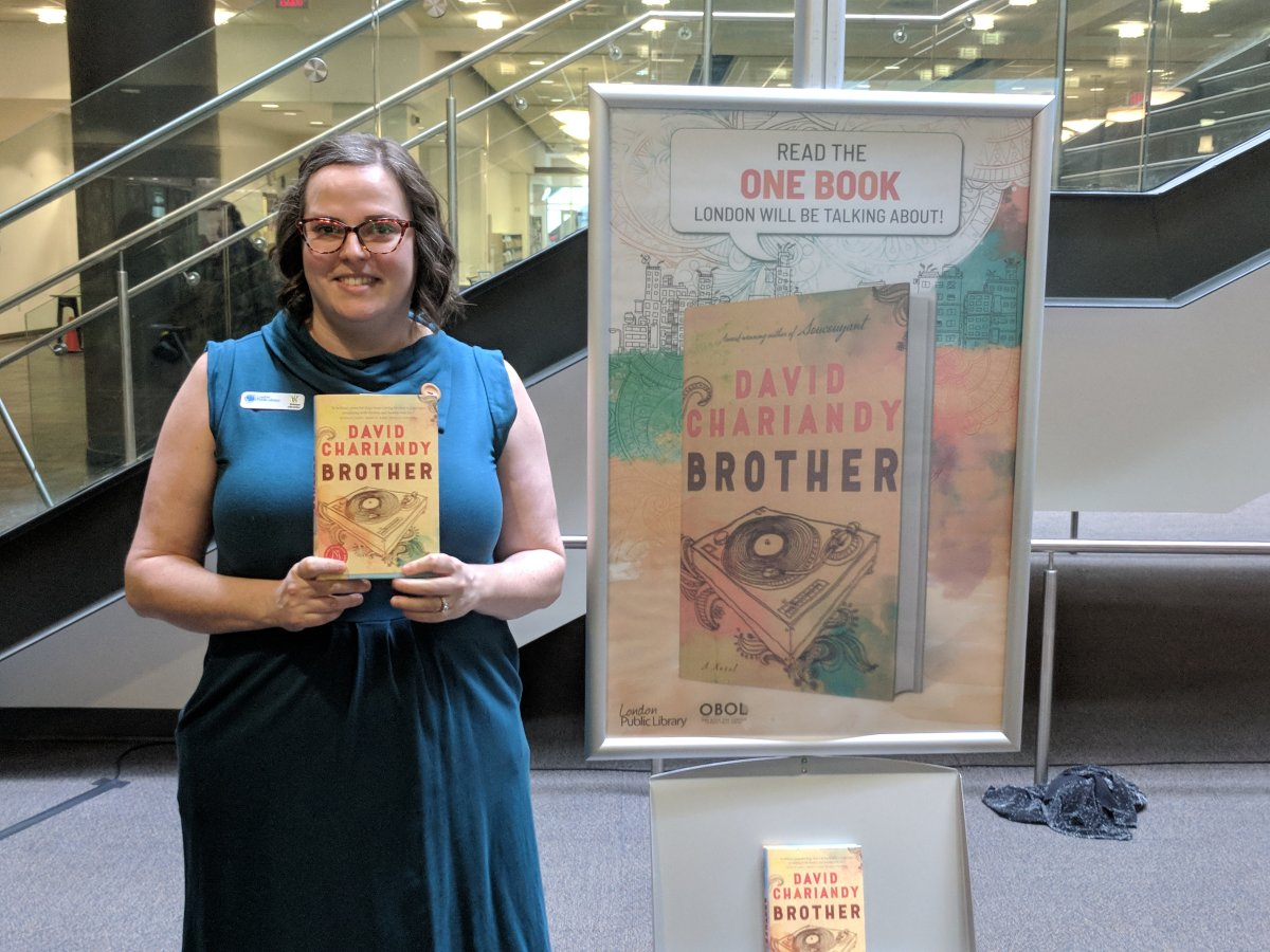 """Librarian Kristen Caschera shows off the title for this year's 'One Book, One London' title, """"Brother"""" by David Chariandy. (Photo by Jake Jeffrey/980 CFPL)."""