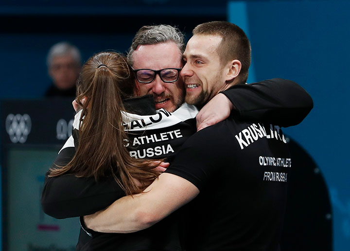 Aleksandr Krushelnitckii and Anastasia Bryzgalova, Olympic athletes from Russia, hug their coach Vasily Gudin after winning the bronze in mixed doubles curling.