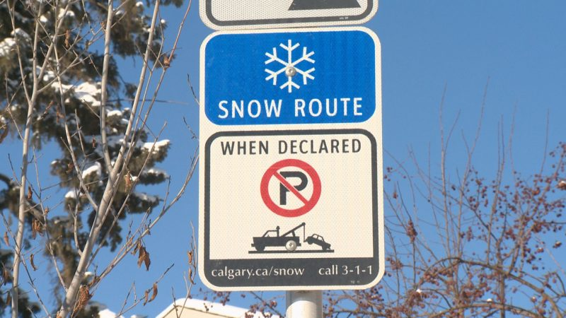 A snow route parking ban sign is shown.