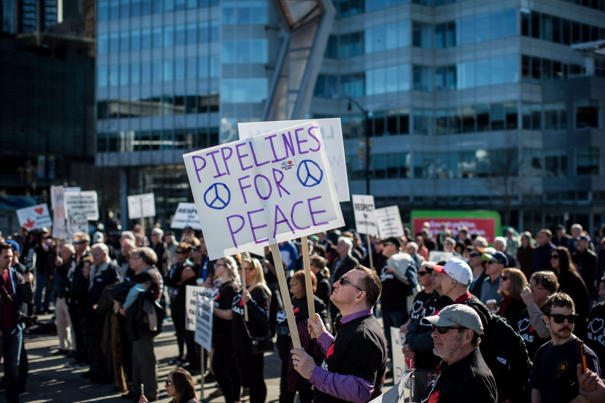 A man holds signs while listening during a rally in support of the Kinder Morgan Trans Mountain pipeline expansion in Vancouver, B.C., on Saturday March 10, 2018.