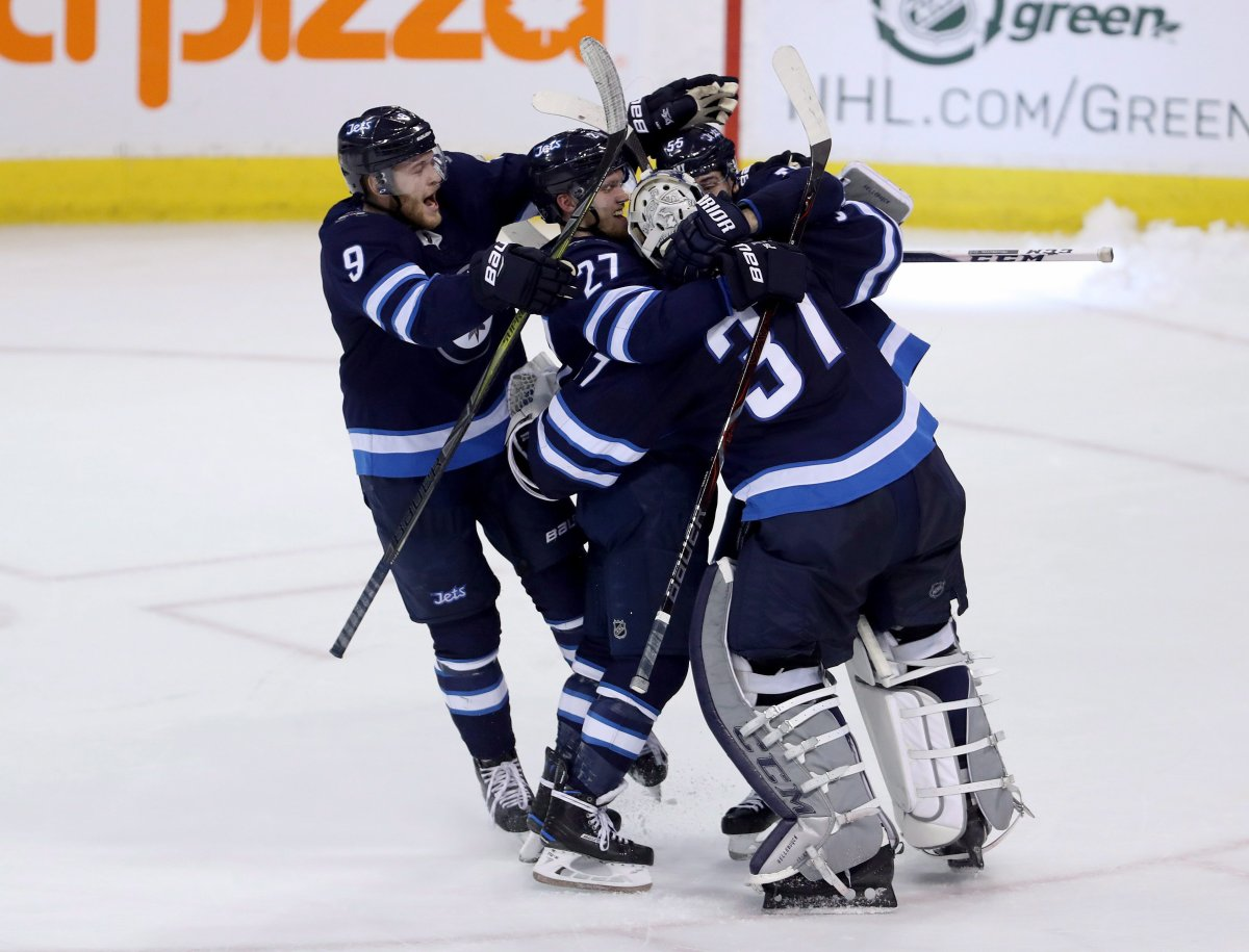 Winnipeg Jets' Andrew Copp (9), Nikolaj Ehlers (27) and Mark Scheifele (55) rush to goaltender Connor Hellebuyck (37) after he made the game-winning save against the Nashville Predators during the shootout following NHL hockey action in Winnipeg, Sunday, March 25, 2018. THE CANADIAN PRESS/Trevor Hagan.