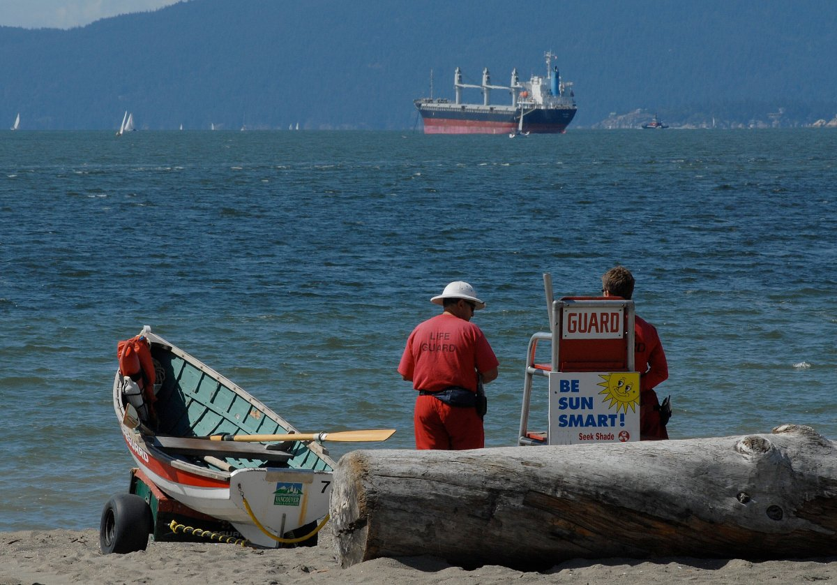 Lifeguards stand next to a rescue boat as they look over English Bay beach in Vancouver, British Columbia, Canada.