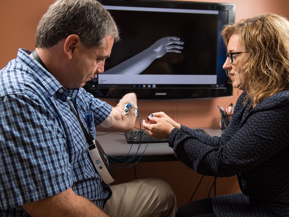 Wendy Hill, a research occupational therapist with the Institute of Biomedical Engineering at the University of New Brunswick (UNB), right, with client Trent Mundie of Fredericton. Hill is one of the researchers at UNB studying whether virtual reality helps ease phantom pain in those that have lost limbs. UNB is first to be holding trials on the potential treatment, for which worldwide clinical testing will be held.