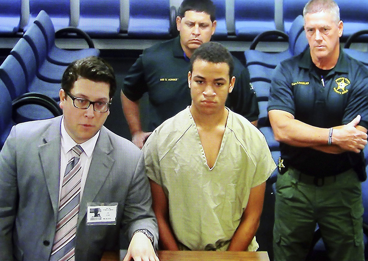 Zachary Cruz, center, the brother of the Florida school shooting suspect, is displayed in a monitor via closed circuit television from the main jail as he as he makes his first appearance on charges of trespassing on the grounds of Marjory Stoneman Douglas High School, Tuesday, March 20, 2018, at the Broward County Courthouse in Fort Lauderdale, Fla.
