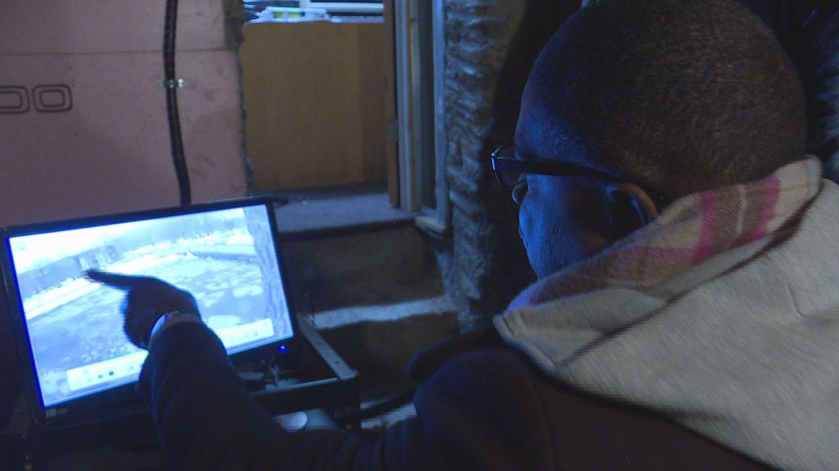 Ariel Jeffrey Kouakou's uncle Charles N'Dakon looks over security footage on March 16, 2018.
