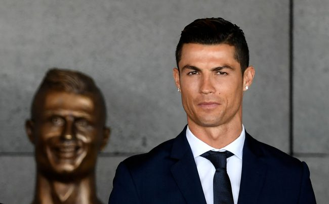 Portuguese footballer Cristiano Ronaldo stands past a bust at the Cristiano Ronaldo International Airport Madeira island, on March 29, 2017.