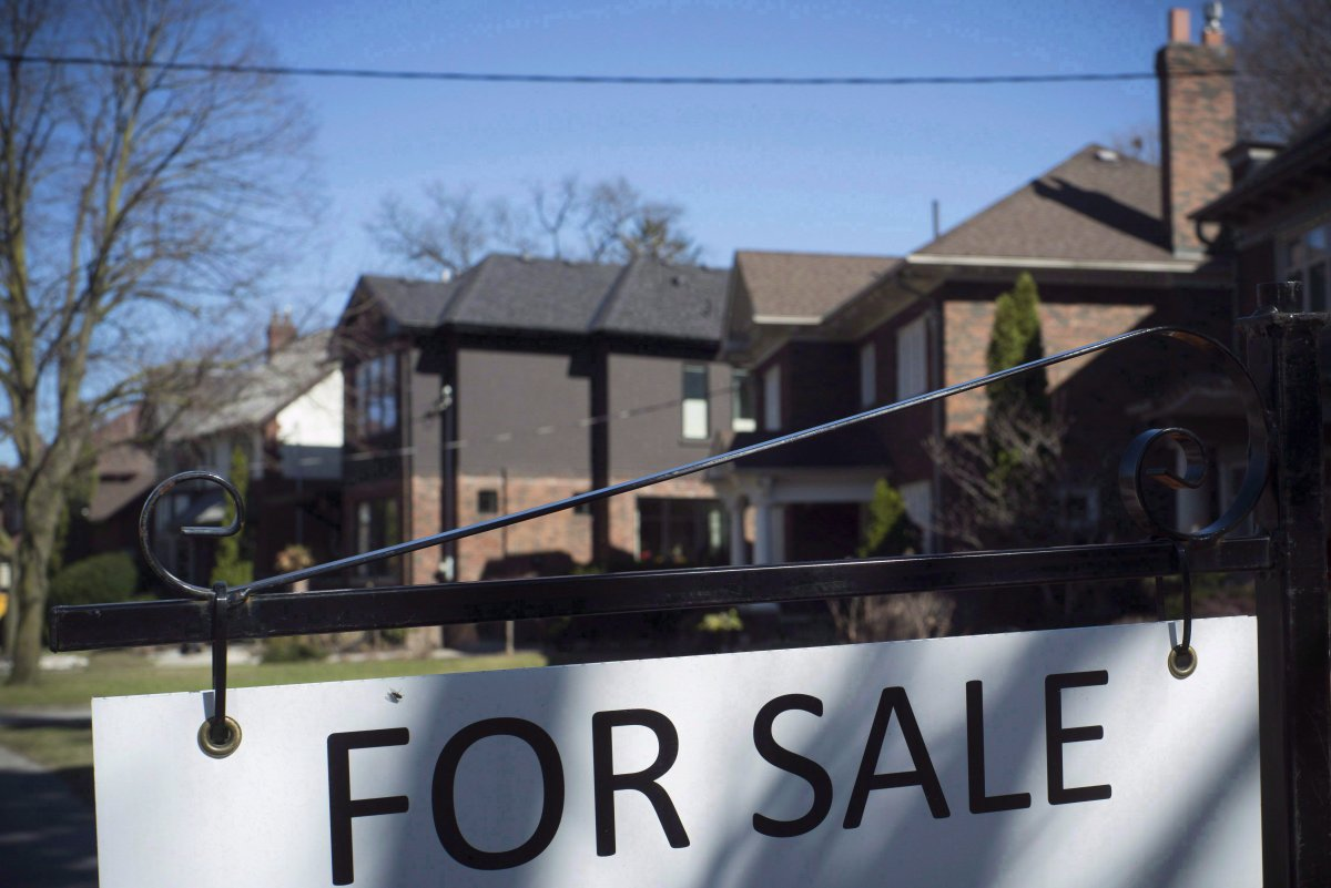 """A """"For Sale"""" sign is shown in front of west-end Toronto homes Sunday, April 9, 2017. The Toronto Real Estate Board says area home sales were up 12 per cent from September to October, pointing to a stronger fall market. THE CANADIAN PRESS/Graeme Roy."""