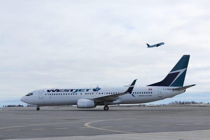 A WestJet Boeing 737 sits on the tarmac as a Air Canada plane take-off from Ottawa International airport.