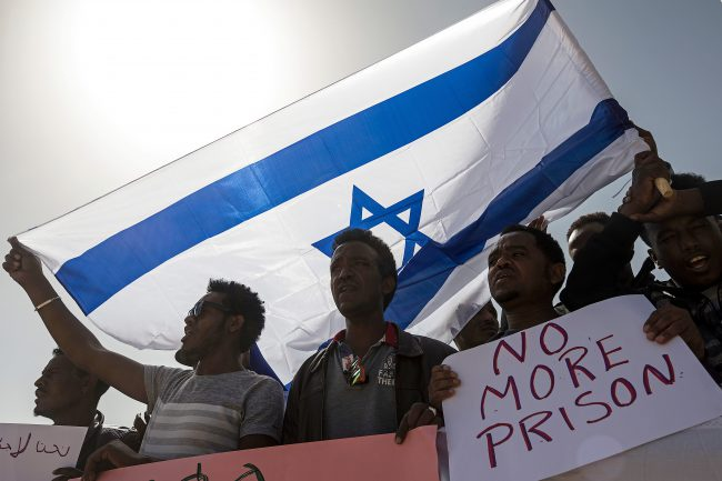 In this Feb. 22, 2018 file photo, asylum seekers march during a protest outside Israeli Prison Saharonim, in the Negev desert, southern Israel.