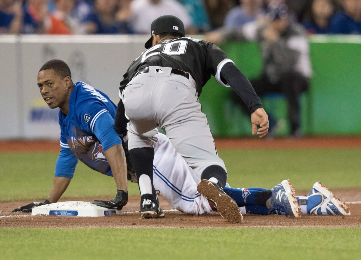 Toronto Blue Jays Curtis Granderson slides safely into third with a triple as Chicago White Sox third baseman Tyler Saladino tries to make a play in the fourth inning of their American League MLB baseball game in Toronto on Tuesday April 3, 2018.