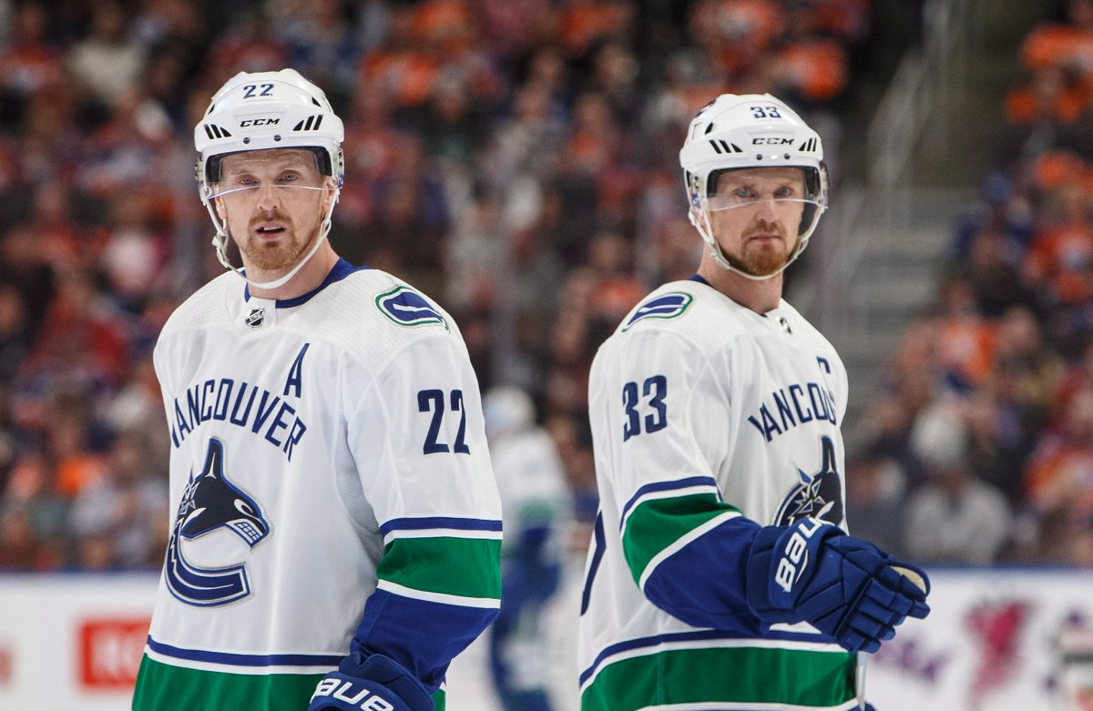 Vancouver Canucks' Daniel Sedin (22) and Henrik Sedin (33) skate past each other against the Edmonton Oilers during first period NHL action in Edmonton, Alta., on Saturday April 7, 2018. THE CANADIAN PRESS/Jason Franson.