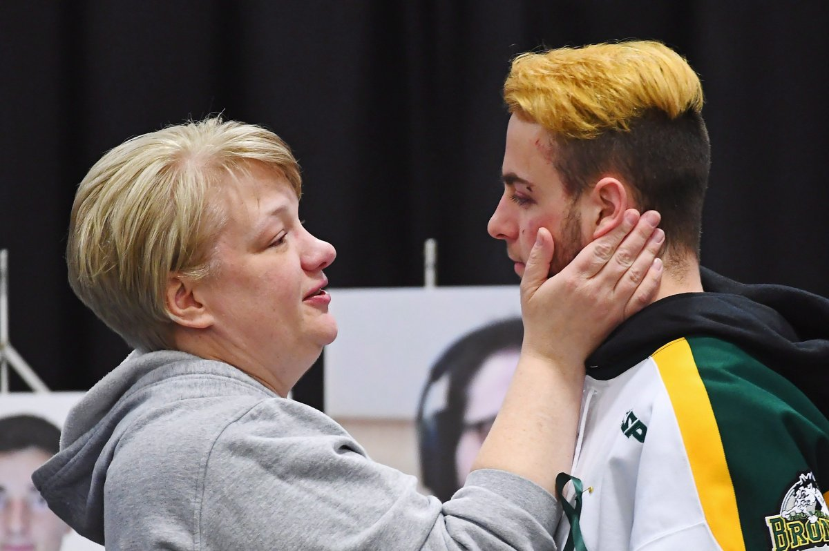 Humboldt Broncos' Nick Shumlanski is comforted by a mourner during a vigil at the Elgar Petersen Arena, home of the Humboldt Broncos, to honour the victims of a fatal bus accident in Humboldt, Sask. on Sunday, April 8, 2018.