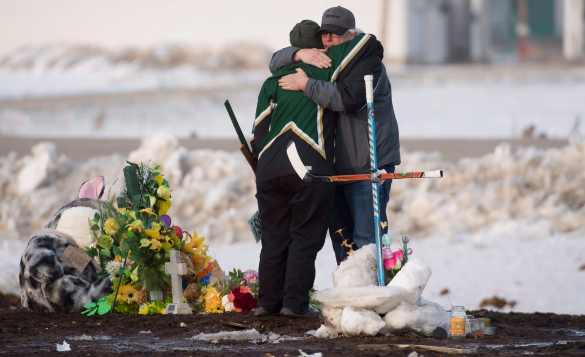 People hug and pay their respects at a makeshift memorial at the intersection of a fatal bus crash near Tisdale, Sask., on Monday, April, 9, 2018. A bus carrying the Humboldt Broncos hockey team crashed into a truck en route to Nipawin for a game Friday night killing 15 and sending over a dozen more to the hospital.