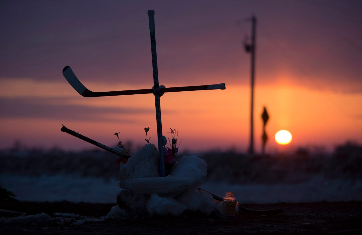 The sun rises across the Prairies as a cross made out of hockey sticks is seen at a makeshift memorial at the intersection of of a fatal bus crash near Tisdale, Sask., Tuesday, April, 10, 2018. A bus carrying the Humboldt Broncos hockey team crashed into a truck en route to Nipawin for a game Friday night, killing 15 and sending more than a dozen more to hospital.
