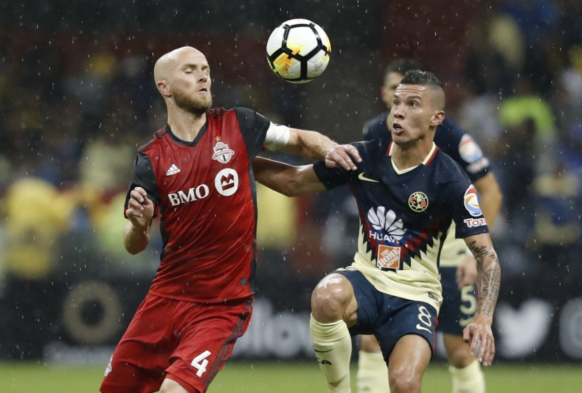 Matias Uribe (R) of America vies for the ball with Michael Bradley (L) of the Toronto FC during the second leg match of the semifinal of the CONCACAF Champions League, at the Azteca Stadium in Mexico City, Mexico, 10 April 2018.