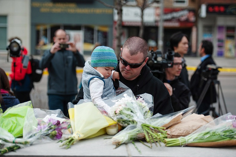 Sean O'Keefe and his son Fionn, 16 months, bring flowers to a memorial on Yonge Street the day after a driver drove a rented van down sidewalks Monday afternoon, striking pedestrians in his path in Toronto, Tuesday, April 24, 2018.