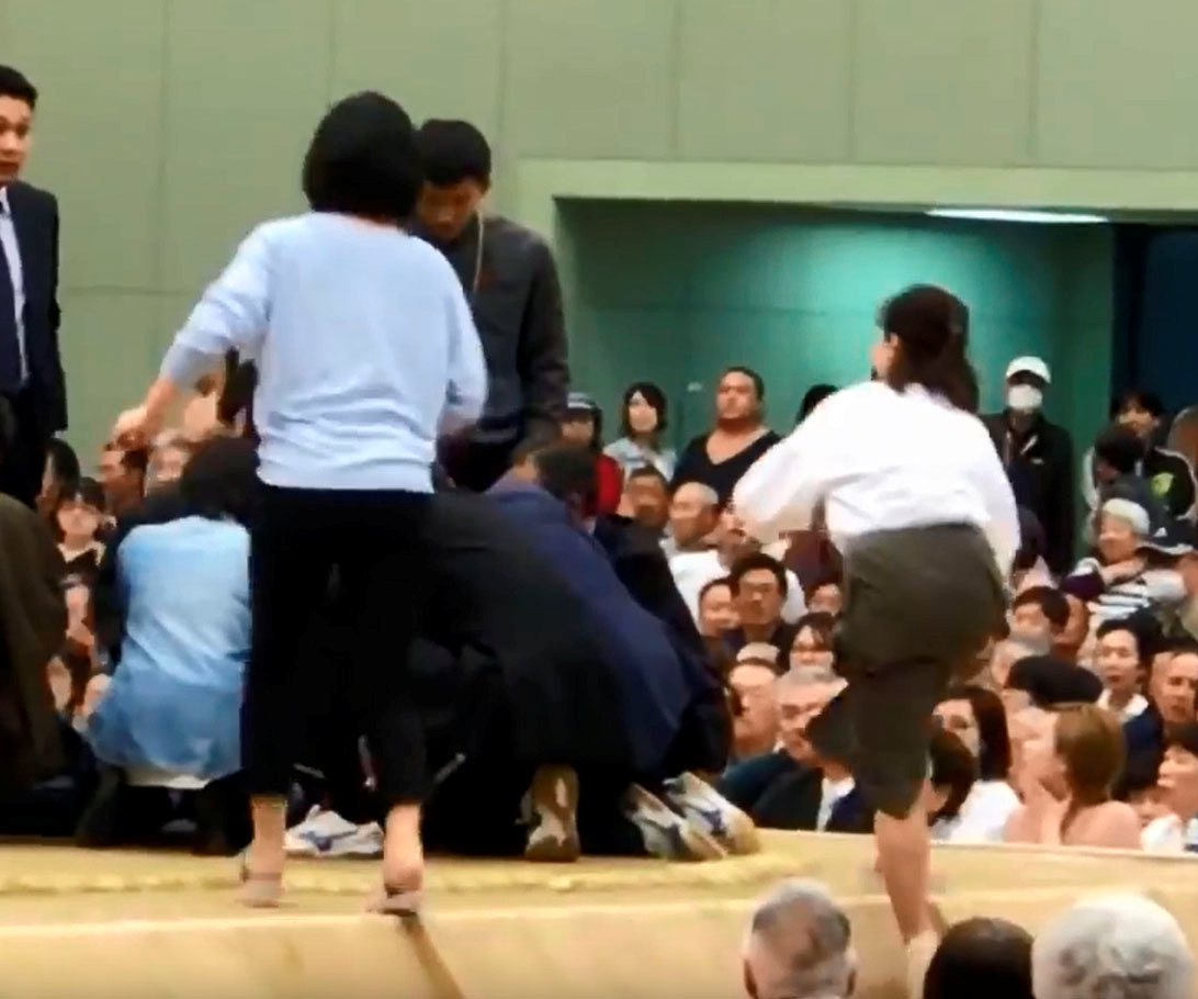 A photo grab from a Youtube video shows women climbing up a sumo ring to treat Maizuru city mayor Ryozo Tatami, who collapsed while making a speech in a gym in Maizuru, Kyoto prefecture, Japan April 4, 2018 in this photo released by Kyodo.