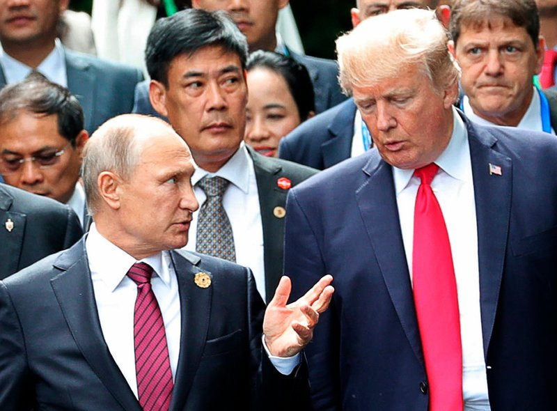U.S. President Donald Trump, right, and Russia President Vladimir Putin talk during the family photo session at the APEC Summit in Danang.