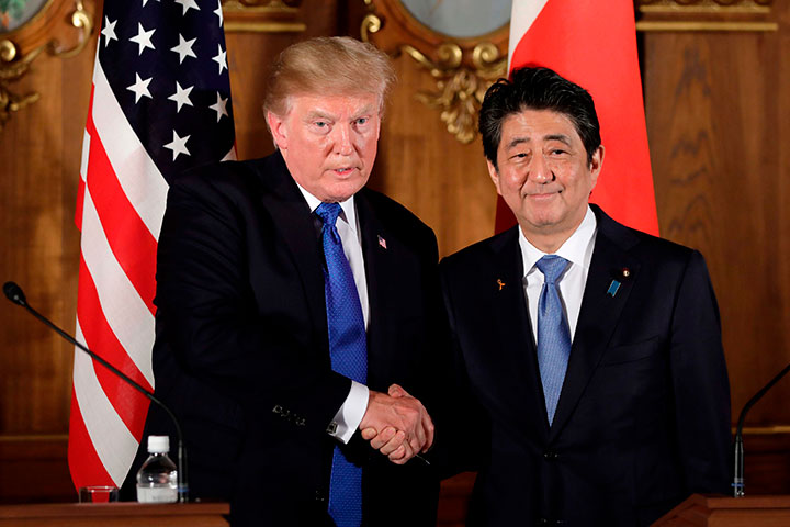 In this Nov. 6, 2017 file photo, U.S. President Donald Trump shakes hands with Japanese Prime Minister Shinzo Abe during a joint news conference at the Akasaka Palace, in Tokyo.