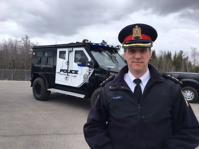 Deputy Police Chief Martin Gaudet poses with the Fredericton Police Force's new armoured vehicle on April 19, 2018, .