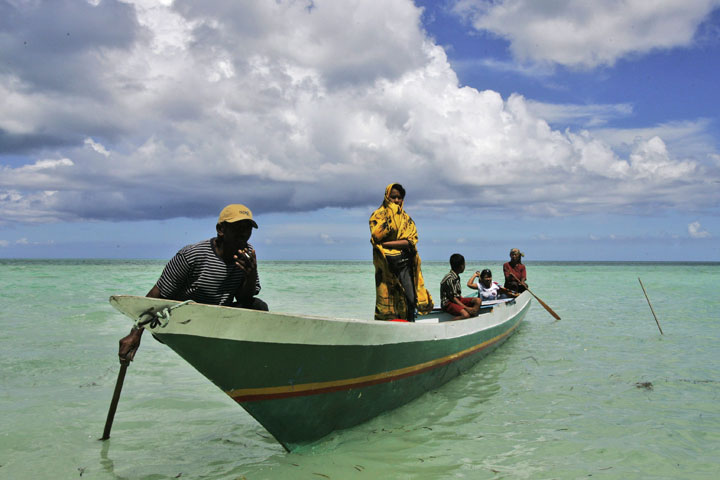 In this Tuesday, April 28, 2009 photo, a fisherman family of Bajau tribe is seen on their boat near Kapota island, Wakatobi waters, Southeast Sulawesi, Indonesia.