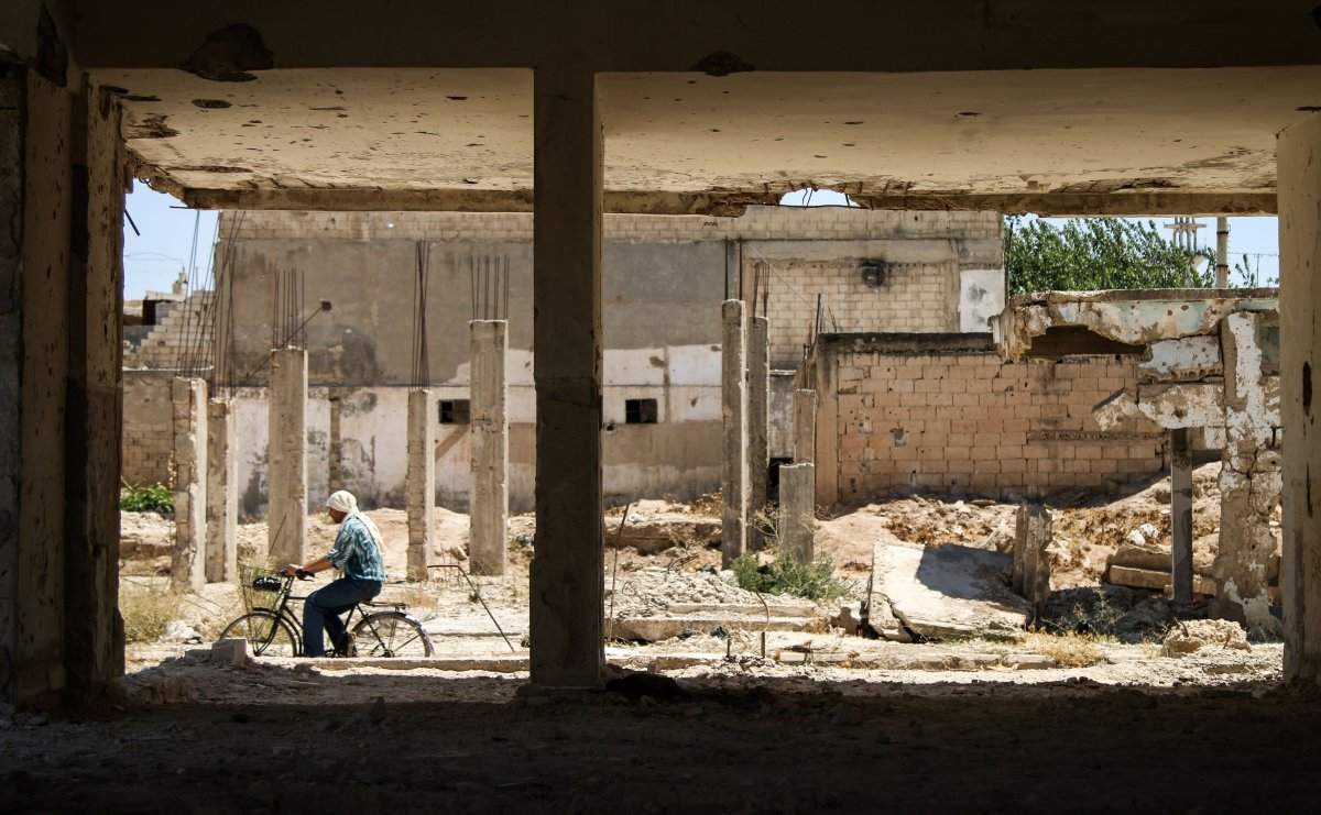 A man rides a bicycle down a street past a damaged building in the central Syrian rebel-held town of Talbiseh, north of Homs, on August 3, 2017.  A ceasefire between government forces and rebels went into effect in part of central Syria on August 3, 2017 after Russia struck a deal with the opposition on a safe zone in the northern parts of Homs province.  The truce is the third to be established in Syria, which has been ravaged by six years of civil war that have left more than 300,000 people dead. / AFP PHOTO / MAHMOUD TAHA        (Photo credit should read MAHMOUD TAHA/AFP/Getty Images).