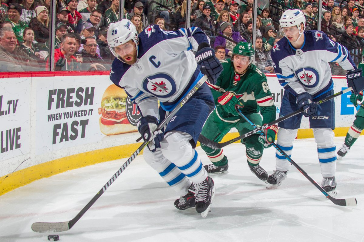Blake Wheeler and Bryan Little of the Winnipeg Jets battle for the puck with Mikael Granlund of the Minnesota Wild during a game earlier this year. The Wild cut the Jets first-round series lead in half Sunday after a 6-2 victory.