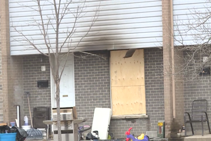 The front window of a townhouse on Curtis Cres. in Kingston is boarded up after a Thursday morning fire left its 7 occupants homeless.