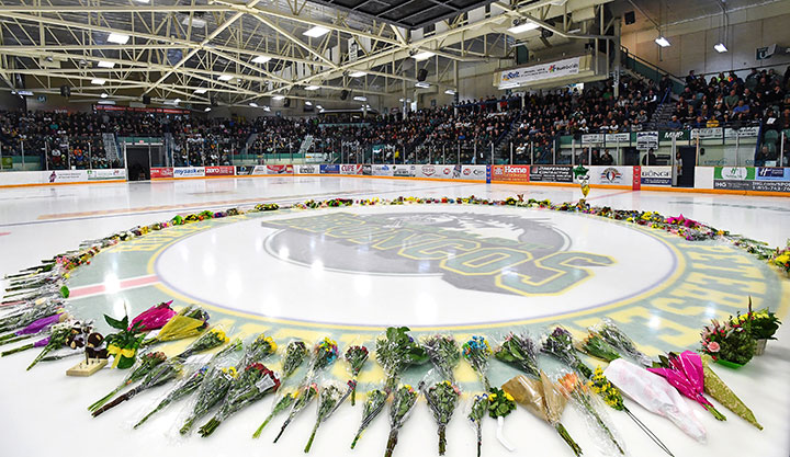 Flowers lie at centre ice as people gather for a vigil at the Elgar Petersen Arena, home of the Humboldt Broncos, to honour the victims of a fatal bus accident, April 8, 2018.