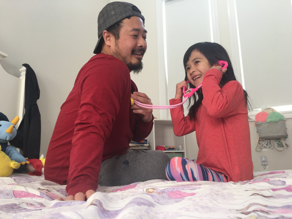 """Olivia Chan (right) uses her play stethoscope to """"listen"""" to the heartbeat of her father, Justin Chan (left)."""