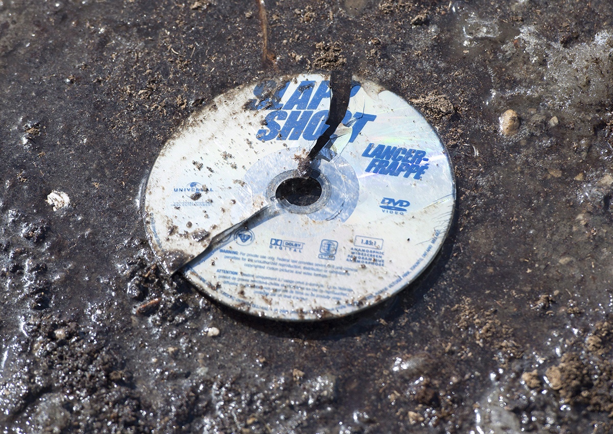 A broken DVD of the hockey movie Slap Shot is seen in the mud at the intersection of a crash site near Tisdale, Sask., Sunday, April 8, 2018.
