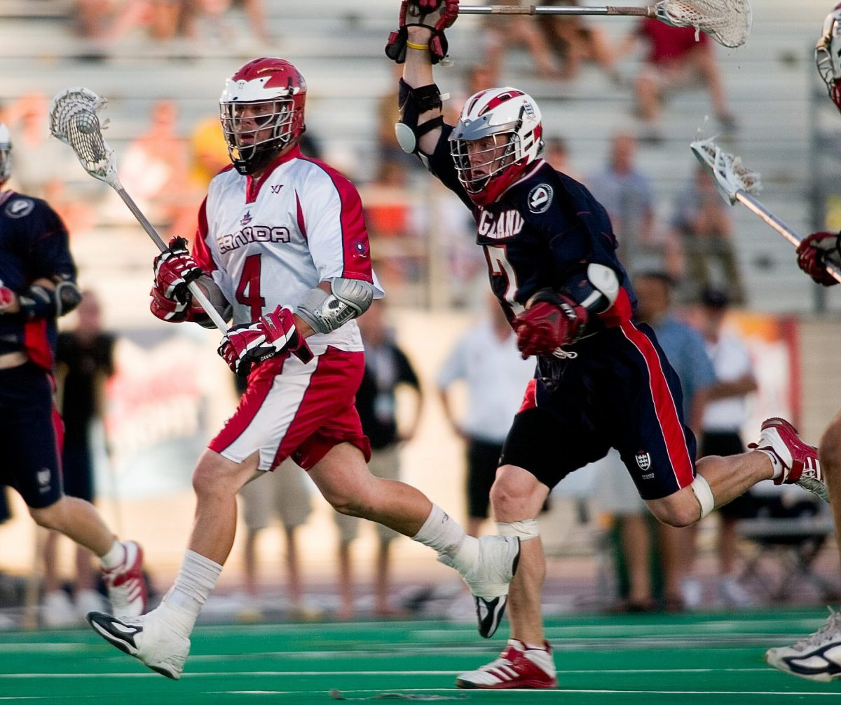 England's Alistair Wallace, right, chases Canada's Geoff Snider at the World Lacrosse Championships In London, Ontario on Tuesday July 18, 2006. Canada defeated England 17-9. (CP PHOTO/Geoff Robins).