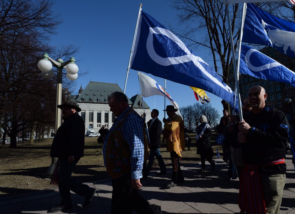 File - David Chartrand, president of the Manitoba Metis Federation, middle, carries the Metis flag as he and fellow Metis Federation leaders and delagates march to the Supreme Court of Canada in Ottawa on Thursday, April 14, 2016.