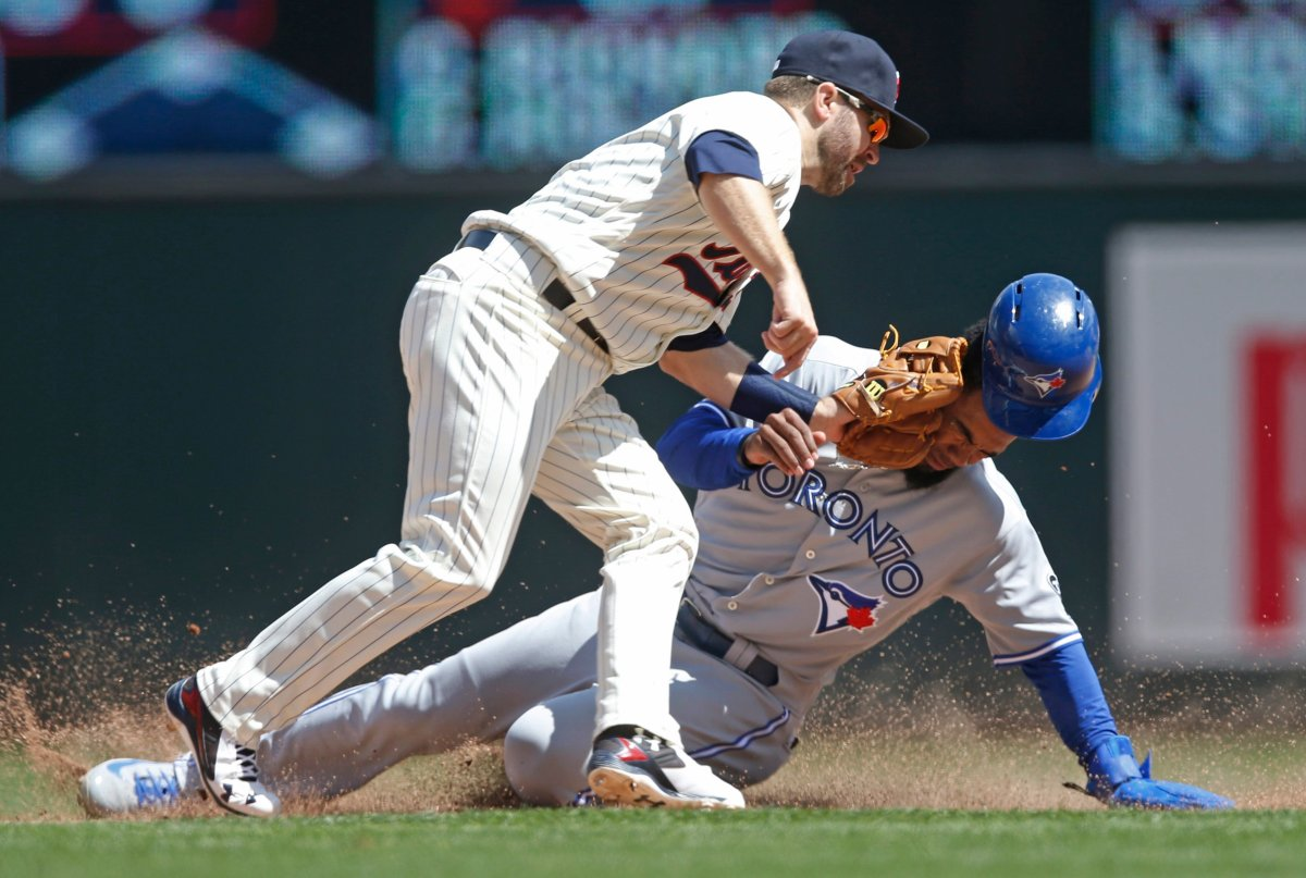 Toronto Blue Jays' Teoscar Hernandez, right, loses his helmet as he is tagged out by Minnesota Twins second baseman Brian Dozier during a steal attempt in the eighth inning of a baseball game Wednesday, May 2, 2018, in Minneapolis. The Twins won 4-0.