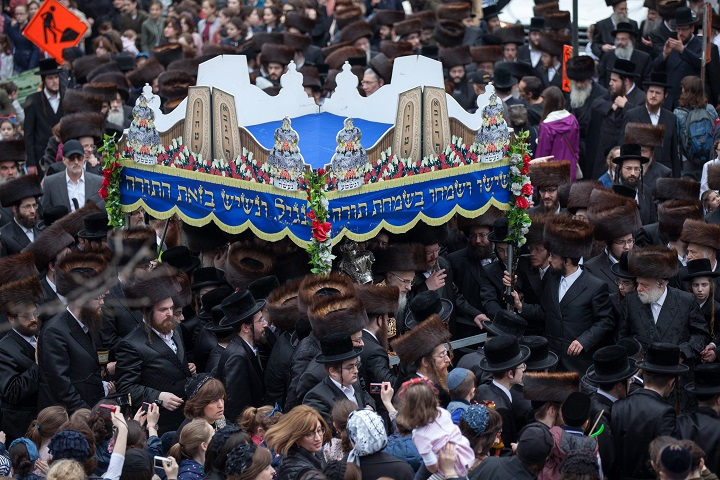 Jewish believers gather during a Hachnasat Sefer Torah parade in Montreal, Canada on May 3, 2018. Montreal's Belz Hasidic Jewish community organized the parade for the new Torah Scroll on the streets of Outremont in Montreal. The Belz community is celebrating the visit of Rabbi Yissachar Dov Rokeach, the leader of the Belz ultra-Orthodox Jewish community who landed in Montreal on Tuesday, May 1, 29 years after his visit in 1989.