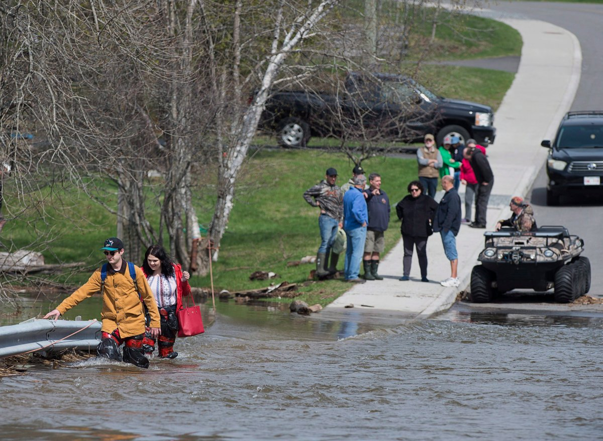Simon Barton, left, and Chelsea Burley wear make shift waders of garbage bags and packing tape as they cross a flooded road in Saint John, N.B. on Sunday, May 6, 2018. Swollen rivers across New Brunswick are still rising, flooding streets and properties and forcing people from their homes in several communities.