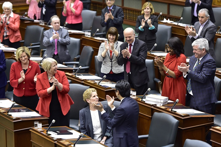 Ontario Premier Kathleen Wynne is applauded by her caucus after finishing her speech at Queen's Park Legislature in Toronto on Tuesday, .