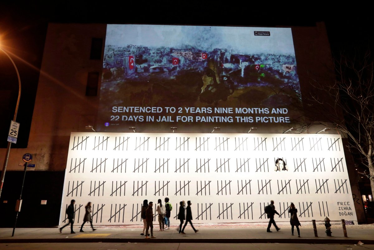 """People pass by a mural by British graffiti artist Banksy protesting the imprisonment of Turkish artist Zehra Dogan in New York on March 16, 2018. An unauthorized exhibition featuring the work of mysterious British graffiti artist Banksy is headed to Toronto. Organizers say """"The Art of Banksy"""" will make its North American premiere in the city on June 13 at 213 Sterling Road. Banksy's former agent, Steve Lazarides, curated the exhibit."""