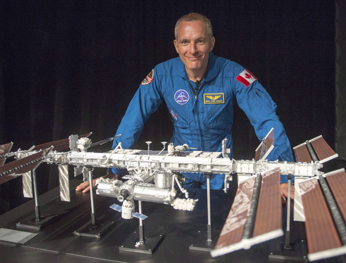 Canadian astronaut David Saint-Jacques looks at a model of the International Space Station at the Canadian Space Agency headquarters in Saint Hubert, Que. on Wednesday, November 29, 2017. Smoked salmon, shrimp cocktails, pate, chocolate fondue and maple syrup are all headed for space.Those tasty foods will be part of David Saint-Jacques' menu during the Canadian astronaut's upcoming six-month stay on the International Space Station.