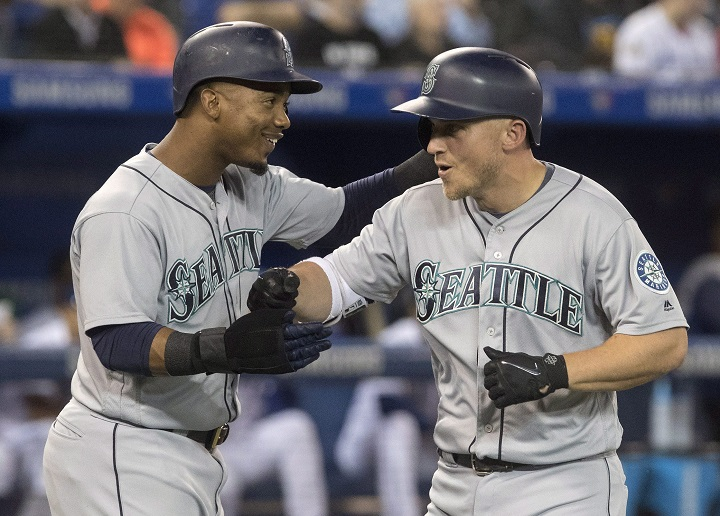 Seattle Mariners' Kyle Seager celebrates with teammate Jean Segura after hitting a grand slam against Toronto Blue Jays starting pitcher J.A. Happ in first inning League MLB baseball action in Toronto on Thursday.