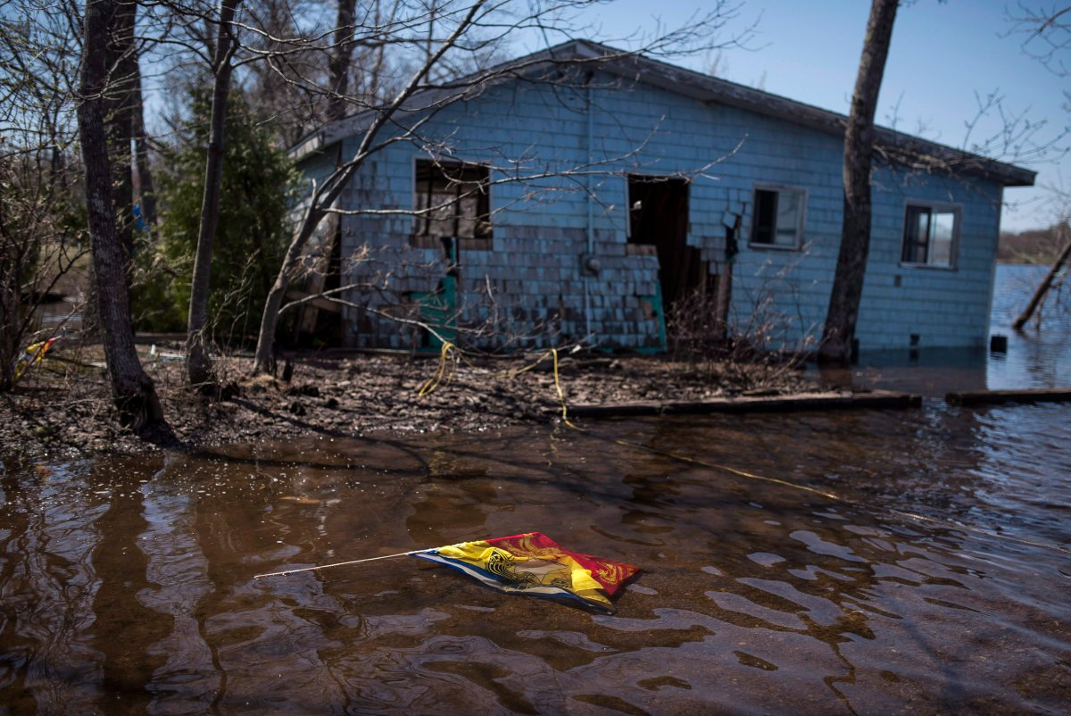 A New Brunswick flag floats in front of a cottage destroyed by flooding from the Saint John River in Waterborough, N.B., on Sunday, May 13, 2018.