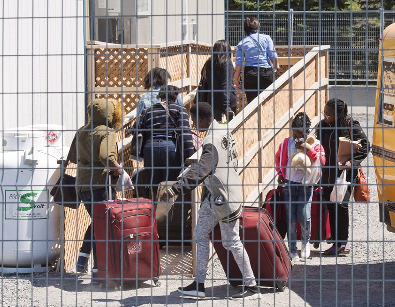 A group of asylum seekers arrive at the temporary housing facilities at the border crossing, Wednesday May 9, 2018 in St. Bernard-de-Lacolle, Que. Almost 96 per cent of asylum seekers who have crossed illegally into Canada so far in 2018 have done so through the Quebec border.