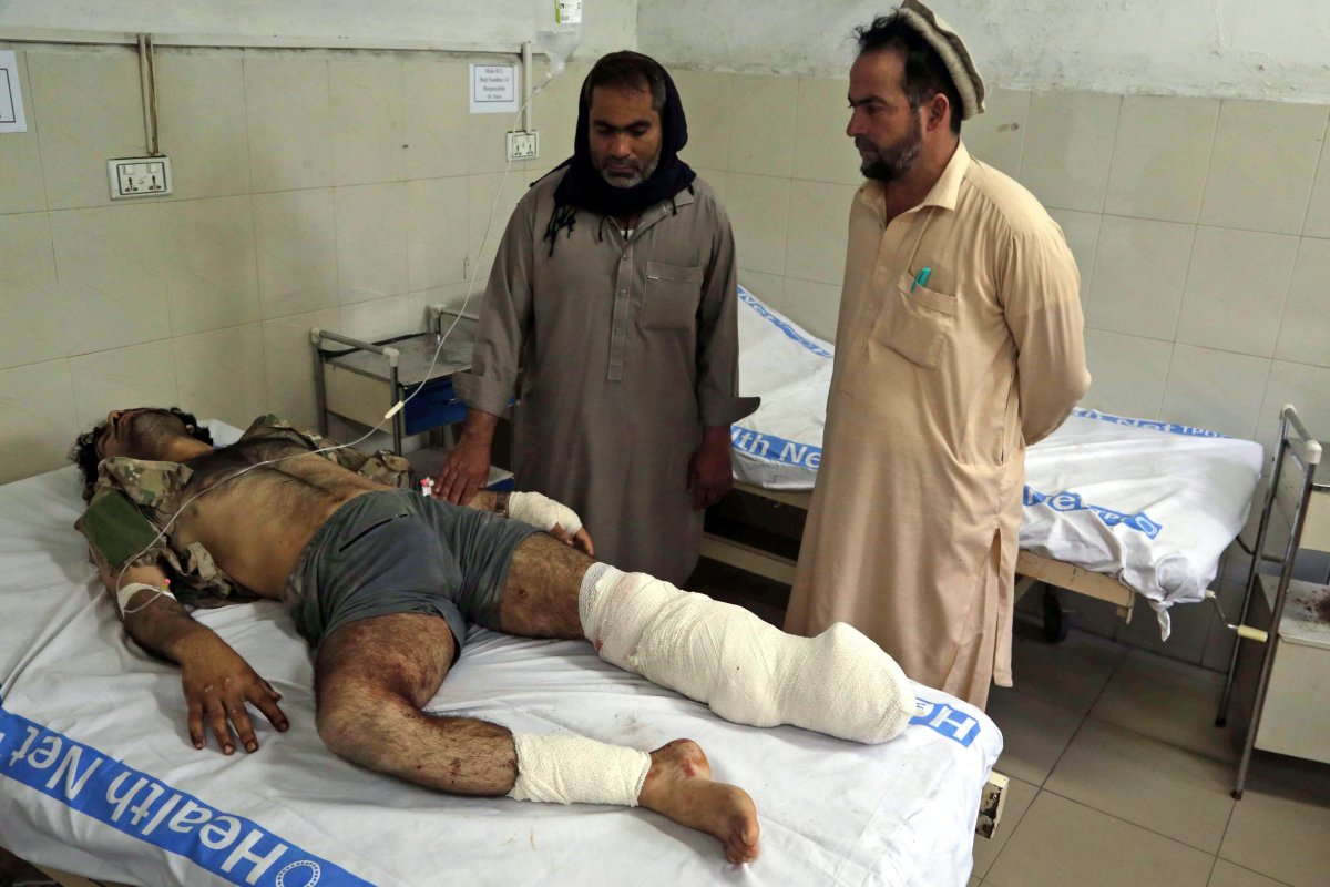 A man who was injured in bomb blasts at a cricket stadium is visited by relatives after having received medical treatment at a hospital in Jalalabad, Afghanistan, 19 May 2018. A  .