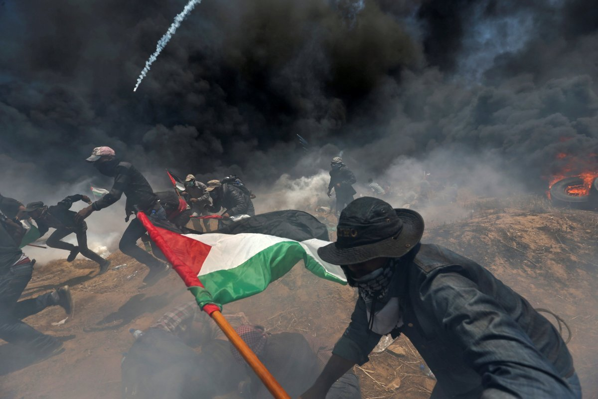 Palestinian demonstrators run for cover from Israeli fire and tear gas during a protest against U.S. embassy move to Jerusalem and ahead of the 70th anniversary of Nakba, at the Israel-Gaza border in the southern Gaza Strip, May 14, 2018.