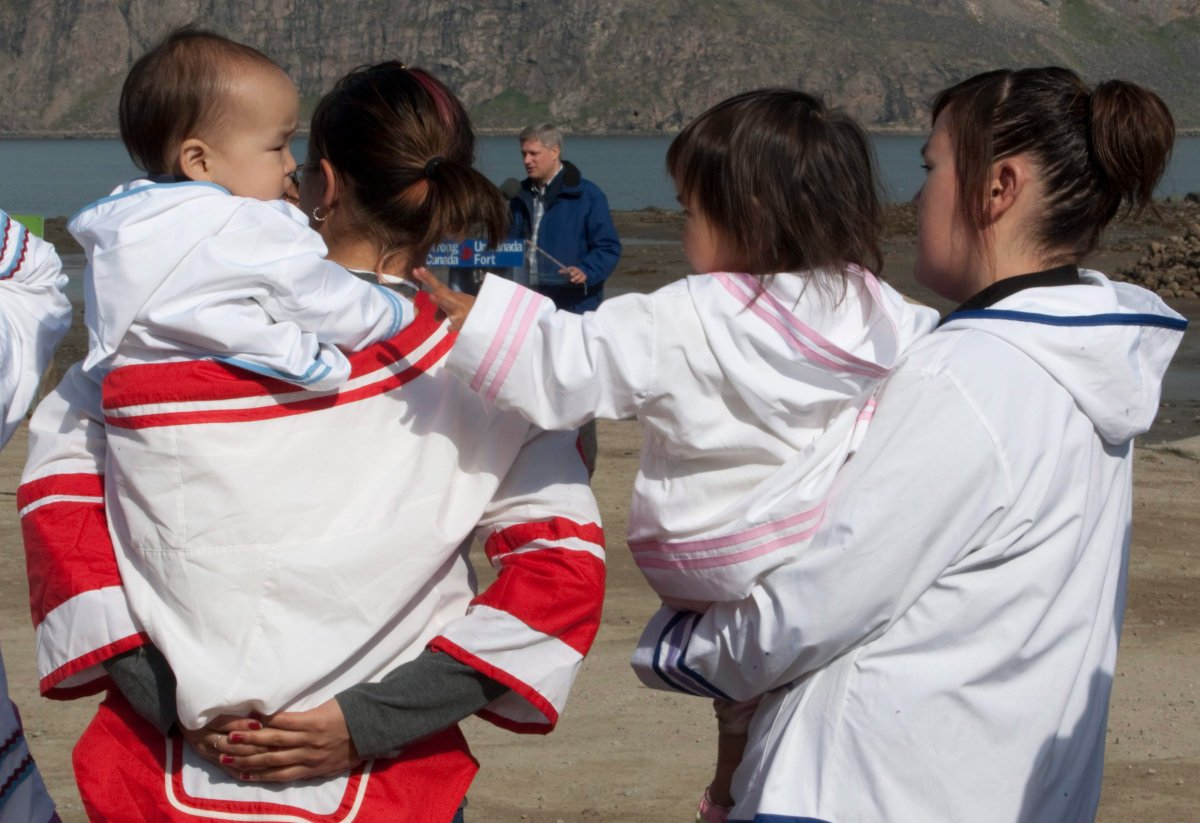 Local women look after young children as Prime Minister Stephen Harper makes an announcement in Pangnirtung, Nunavut Thursday, Aug. 20, 2009.