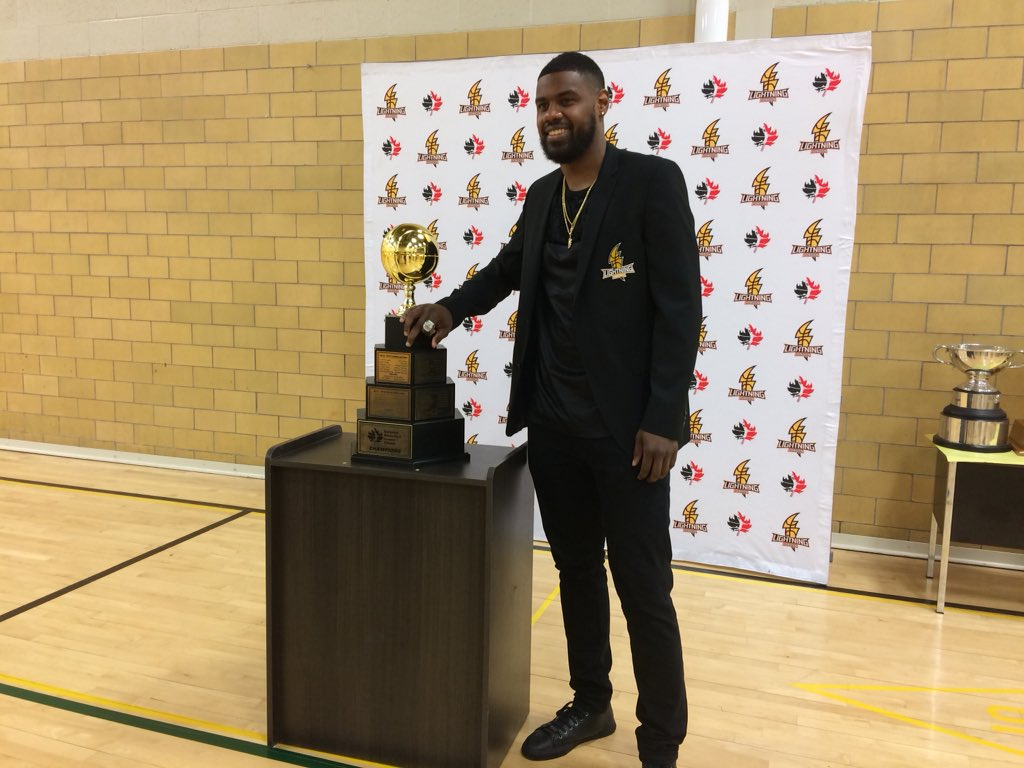 London Lightning shooting guard Kyle Johnson stands with the NBL Championship trophy.