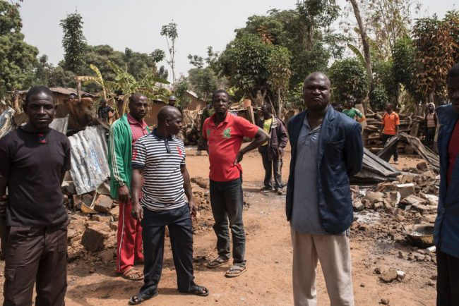 This Feb. 24, 2017 photo shows men standing among rubbles in the village of Bakin Kogi in Nigeria's Kaduna state after an attack.